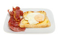 Poached egg and bacon on toast with crispy on a plate isolated against white Stock Images