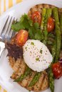 Poached egg on toasted bread with asparagus tomatoes and greens Stock Photo