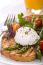 Poached egg on toasted bread with asparagus tomatoes and greens served fresh orange juice Royalty Free Stock Photos