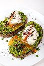 Poached eggs with avocado guacomole on brown bread with sesame seeds. Healthy breakfast on a white background. Royalty Free Stock Photo