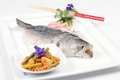 Poached sea bass whole barramundi served on a white plate Royalty Free Stock Photo
