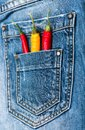 Pocket of jeans staffed with red and yellow chilly peppers, denim background. Piquant secret in pocket of pants, top Royalty Free Stock Photo