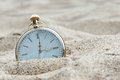 Pocket watch buried in sand antique Stock Image