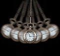 Pocket watch swinging on a chain black background silver to hypnotise Stock Images