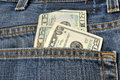 Pocketful of money coming out the back pocket a pair blue jeans Royalty Free Stock Photo