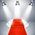 Podium with red carpet on three elevated circular steps a illuminated by three spotlights for an important event public speaking Stock Photo