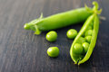 Pods of green peas and pea on a wooden surface Royalty Free Stock Photo