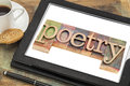 Poetry word typography text in letterpress wood type on a digital tablet with a cup of coffee Royalty Free Stock Photos