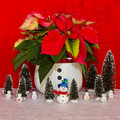 Poinsettia in a white basket with snowman and trees red Royalty Free Stock Photography
