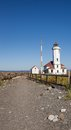 Point wilson lighthouse walkway on the edge of landsend the is an historical structure near port townsend washington gleaming Stock Image