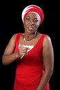 Pointing finger african lady dressed in a red dress and fitting headscarf her in anger and frustration isolated on a black Stock Image