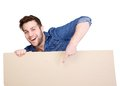 Pointing finger to blank poster sign portrait of a happy young man smiling and copy space on Royalty Free Stock Images