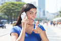 Pointing latin woman with long dark hair at phone in city Royalty Free Stock Photo