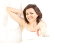 Pointing you young woman relaxing in white bedding Royalty Free Stock Image