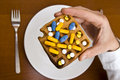 Poisons for eating human hand hold waffle with pills from top view Royalty Free Stock Images
