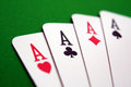 Poker aces playing cards four over green table Royalty Free Stock Images
