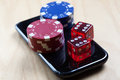 Poker Chips and Dices on top of cell phone Stock Photos