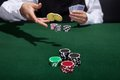 Poker player increasing his stakes throwing tokens onto the gaming table to meet or beat opponents wager to stay in the game Stock Photography