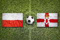 Poland vs. Northern Ireland flags on soccer field Royalty Free Stock Photo