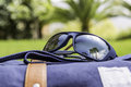 Polarized sunglasses and backpack reflection of palms beach on over a travel focus on the right lense travel concept Royalty Free Stock Photo