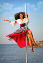 Pole dance girl in dress and hat sexy against sea background Royalty Free Stock Images