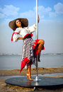 Pole dance girl in dress and hat sexy against sea background Royalty Free Stock Photos