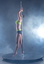 Pole dance harmonous girl posing in spotlights on background of Royalty Free Stock Image