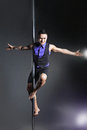 Pole dance man over black background with flashes young strong Royalty Free Stock Photography