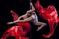 Pole dance young beautiful woman sportive flexible dark background and red silks Stock Photo