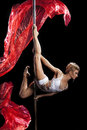 Pole dance young beautiful woman sportive flexible dark background and red silks Stock Images