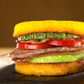 Polemta burger with beef zucchini tomato and bacon polenta fried selective focus focus on the front of the Royalty Free Stock Photography