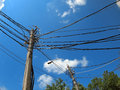 Poles with a lot of wires and electric lamps lighting against blue sky wide angle distortion view Stock Photography