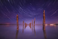 Poles in the water at night on with star trails unusual a background sky Stock Photos