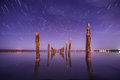 Poles in the water at night with star trails unusual on a background sky Royalty Free Stock Images