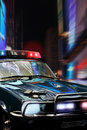 Police car at night in new york city gun cartridges and badge rest on the hood which reflects the edifices and lights of Royalty Free Stock Photo