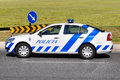 Police car portuguese next to traffic signs and a green field Stock Image