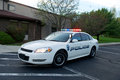 Police car white american sedan with red blue lights on Royalty Free Stock Image