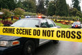 Police cars at crime scene behind taped barrier Royalty Free Stock Photo
