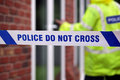 Police crime scene investigation do not cross boundary tape investigating policeman Stock Photo
