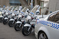 Police cycles lined behind police car. Royalty Free Stock Image