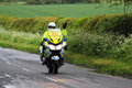 Police motor cyclist waving a moving along a country road in the united kingdom and at the photographer Stock Photos