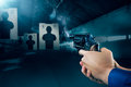 Police officer firing a gun at a shooting range / dramatic light Royalty Free Stock Photo