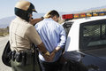 Police Officer Guiding Apprehended Man Into Police Car Royalty Free Stock Photo