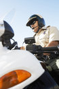Police officer sitting on motorcycle low angle view of a against the sky Stock Images