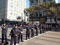 Police officers stand in line across market street Stock Image