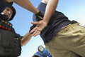 Policeman arresting criminal against sky low angle view of Royalty Free Stock Photo