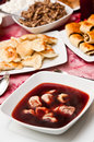 Polish christmas table traditionally set red borsch with dumplings in the foreground Royalty Free Stock Photography