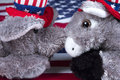 Political party face off republican elephant and democrat donkey nose to nose in front of an american flag Royalty Free Stock Images