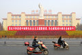 Political slogan in china two men riding a motorcycle pass by a chinese and mao zedong statue at tian fu square chengdu Stock Image