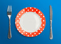 Polka dot red plate with fork and knife top view on blue background Stock Image